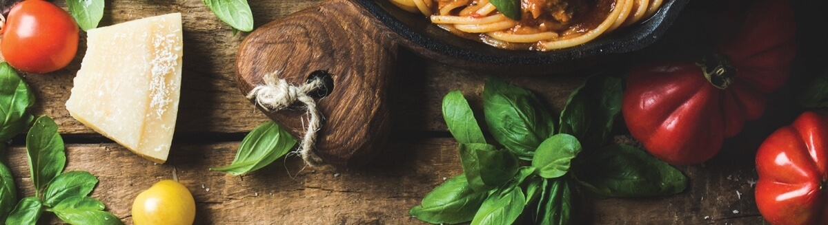 Arrangement of pasta and herbs and cheese on a wooden background.
